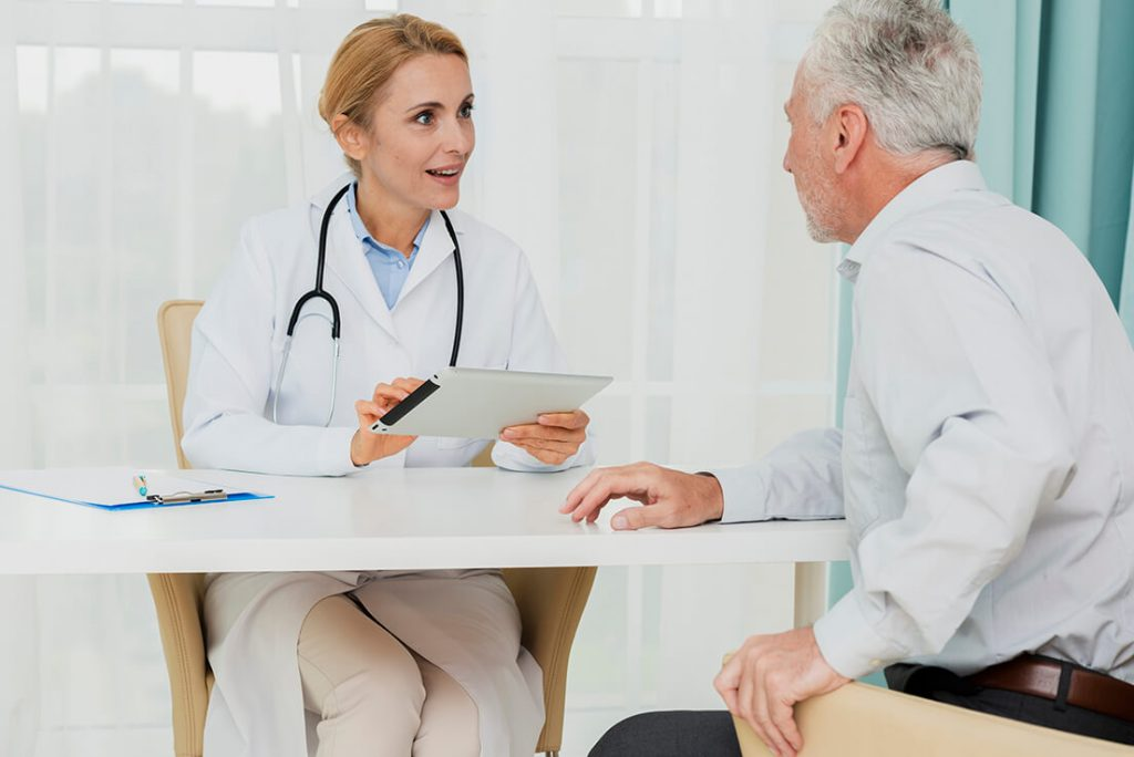 doctor talking patient while holding tablet